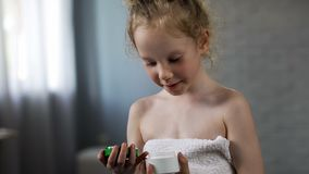 Excited cute little girl holding tube with mothers cream tube, preparing use it. Stock photo stock photo