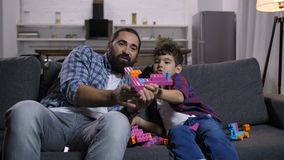 Excited dad and kid playing with colorful toy stock footage