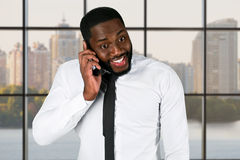 Excited darkskinned guy holding cellphone. Royalty Free Stock Image