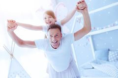 Excited daughter and father playing together. We believe we can fly. Radiant little girl and her cheerful father grinning broadly while having fun and pretending royalty free stock image