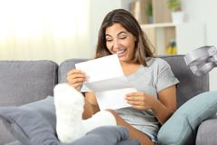 Excited disabled girl reading a paper letter at home. Excited disabled girl reading good news in a paper letter sitting on a couch at home royalty free stock images