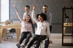 Excited diverse colleagues having fun riding oh chairs in office. Happy coworkers employees enjoying funny game playing and laughing together at work break Royalty Free Stock Image
