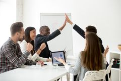 Excited diverse colleagues or partners giving high-five at team. Excited diverse executive colleagues or partners giving high five at team meeting, happy smiling Royalty Free Stock Photo