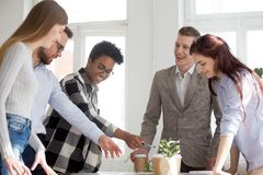 Excited diverse employees have fun brainstorming in office. Excited multiracial colleagues have fun brainstorming at meeting, talking or explaining, diverse royalty free stock image