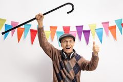 Excited elderly man at a party with a cane stock photo