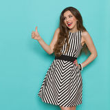 Excited Elegant Woman Showing Thumb Up. Shouting attractive woman in black and white striped dress showing thumb up and looking away, Three quarter length studio Royalty Free Stock Image