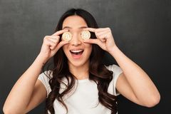 Excited emotional asian young woman holding two golden bitcoins covering eyes. Image of excited emotional asian young woman standing isolated over black wall Stock Image