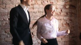 Excited employees celebrating success with funny victory dance in office. Excited happy employees dancing in office near workplace, positive young man and woman stock video footage