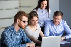 Excited employees looking at laptop observing growing statistics. Smiling employees looking at laptop excited by company growing statistics and market success stock photography