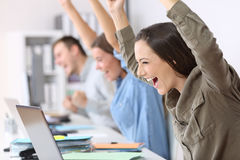 Excited employees receiving good news on line. Three excited employees receiving good news on line in their laptops at office royalty free stock photos
