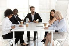 Excited employees watch interns sign contracts at meeting. Excited diverse employees watch new workers sign contract at business meeting in office, female royalty free stock photo