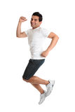 Excited energetic jumping man success. An excited jumping leaping man wearing casual clothes - success victory triumph.  Joyful young person smiling as he Royalty Free Stock Photos