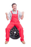 Excited and enthusiastic mechanic shouting for joy. With arms up sitting on a tire royalty free stock photos