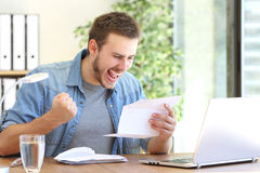 Excited entrepreneur reading a letter. Casual excited entrepreneur reading a letter with good news in a desktop at workplace Royalty Free Stock Photo