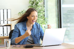 Excited entrepreneur working on line. With a laptop at office and the hair moved by the wind Stock Photo