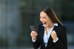 Excited executive reading amazing news on line Stock Photo