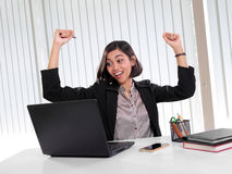 Excited executive woman looking at laptop in her office. Happy Asian female executive raising her arms in excitement while looking at her laptop screen in her Royalty Free Stock Image