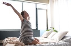 Excited expectant mother waking up in bedroom royalty free stock images