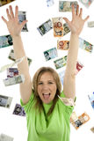 Excited about falling money. Woman with a lime green shirt excited about the money falling around her Royalty Free Stock Images