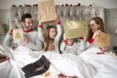 Excited Family In Bed At Home Opening Gifts On Christmas Day royalty free stock photography