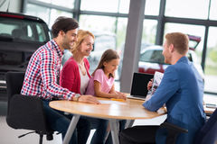 Excited family in car showroom. Listens car agent Stock Image