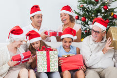 Excited family exchanging gifts at christmas. On the couch Stock Photos