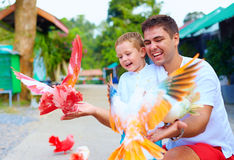 Excited family feeding colorful pigeons on animal farm Royalty Free Stock Image
