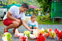 Excited family feeding colorful pigeons on animal farm Royalty Free Stock Photo