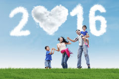 Excited family jumping at field with numbers 2016 Royalty Free Stock Image