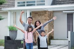 Excited family with kids raised arm. Excited young asian family with kids raised their arm in front of their house Royalty Free Stock Image