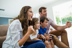Excited family playing video games together in living room Stock Photo