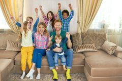 Excited family sitting on couch. Stock Image