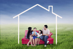 Excited family sitting under dream house Stock Photography