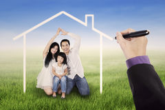 Excited family under a dream house Stock Photos