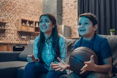 Little boy and his young mother watching tv and cheering while holding a stock photography