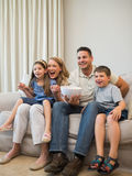 Excited family watching television on sofa. Full length of excited family watching television while sitting on sofa at home Stock Photography