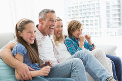 Excited family watching television on sofa Royalty Free Stock Image