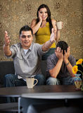 Excited Family Watching TV. Excited men and women with distraught son watching television Stock Photography