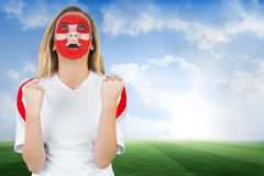 Excited fan in swiss face paint cheering Stock Photo