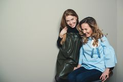Excited fashionable young women having fun together. Two cute girls best friends smiling and embracing. Happy women talking and la stock images