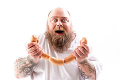 Excited fat bearded man holding sausages Royalty Free Stock Photography