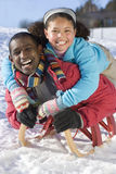 Excited father and daughter sledding down snowy hill on sled Stock Photos
