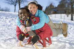 Excited father and daughter sledding down snowy hill on sled Royalty Free Stock Photography