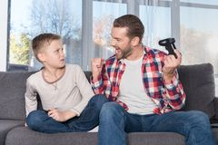 Father and son playing with joysticks. Excited father holding joystick and looking at little son Royalty Free Stock Image