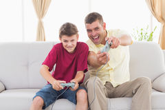 Excited father and son playing video game. Portrait of excited father and son playing video game on sofa at home Stock Photo