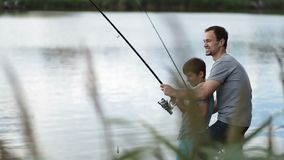 Excited father and son pulling fish out from lake stock footage