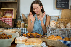 Excited female customer looking at tray of dessert at counter Royalty Free Stock Image