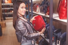 Excited female customer purchasing new handbag in shop Stock Photography