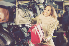 Excited female customer selecting new hand bag. In store Stock Image