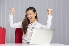 Excited female executive. Screaming and celebrating with raised clenched fists her business victory in front of laptop in the office Royalty Free Stock Image